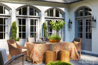 The outdoor dining table is draped with a Moroccan-inspired rug from Moattar Ltd. The chairs are from Restoration Hardware and the stools are from Jerry Pair.