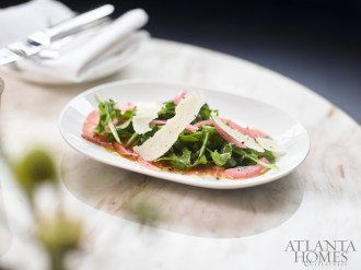 beef carpaccio with arugula, pickled red onion, parmesan, and olive oil.