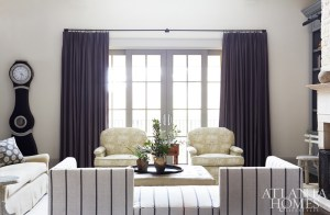 A linen-striped Jacquard fabric from Kravet covers the angled couch in the family room, while charcoal Pindler drapes anchorthe room's warm gray color scheme.