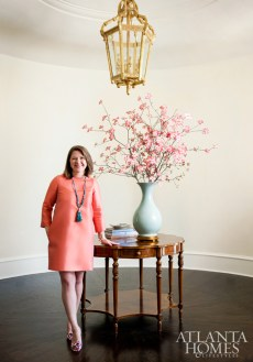 Designer Mallory Mathison Glenn stands in the entry, which features 14-foot ceilings hand covered with Venetian plaster. A handmade lantern from San Francisco anchors the circular space.