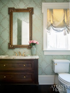 Aqua Cowtan & Tout wallpaper boasts gold-leaf vines and leaves in a trellis pattern, while an onyx countertop—more durable than marble—complements the print with its honey, ivory, gold and soft-aqua veining.