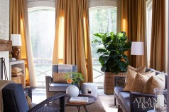 The screened loggia feels more like an interior space. The drapery, fabricated by Douglass Workroom, features both Sunbrella and Schumacher fabric. Stools, Lee Industries through Bungalow Classic. Coffee table, Arteriors through Bungalow Classic. Stools, Emissary.