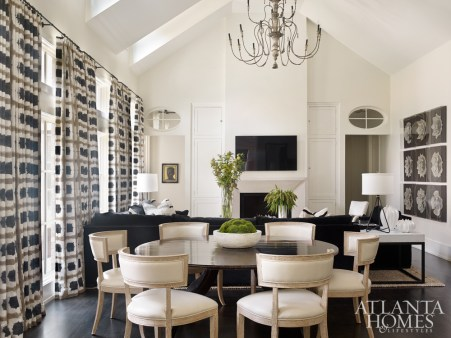 Style meets function in the combination living-dining room of this Buckhead residence by interior designer Melanie Turner and associate Jill Tompkins. To keep the aesthetic masculine, stylish, but also fresh, they began by selecting a bold Scion fabric for the draperies; its pared down color palette influenced the home's overall design direction. The dining table is by Amy Howard and the Klismos chairs are by Global Views.