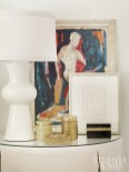 A bedside table features a sculptural Arteriors lamp and an antique painting.