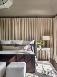 In the master bedroom, a curtained wall adds softness.Webb dressed up the existing bed with bedding from Peacock Alley and custom pillows.