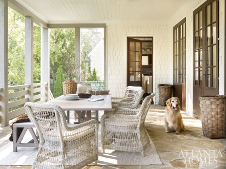 Elegant as any interior space, the porch is a study in natural materials and organic hues, creating a soft and serene scheme. A long, weathered teak table from Janus et Cie anchors the room. It is surrounded by comfortable woven armchairs by Kingsley-Bate. A teak dining bench, also by Janus et Cie, provides plenty of seating for friends and family. The rug is by Dash & Albert. The wicker demijohn is from A. Tyner Antiques.