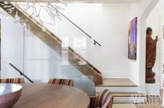 A tempered-glass staircase is a nod to Pritchett and Dixon's love for modern European design. The stairs had to be constructed outside and then set into place by a crane on the second floor. The frameless structure gives the middle of the home an airy effect, letting light from the stairwell skylight fill every corner.