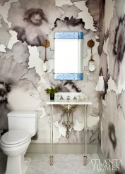 In the formal powder room, a Phillip Jeffries floral and a reverse-etched mirror from Robuck pack in the punch.