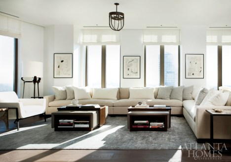 Beauty meets function in living room, where Westbrook designed a custom sectional that's equal parts comfortable and elegant for a family with three tall young adult sons. Here, Troscan's Weekend ottomans with sliding tray details can withstand a put-up-your feet mentality. The framed sketches are by Brian Coleman through Anne Irwin Fine Art.