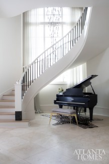 In the foyer, Broaddus selected a leggy brass bench to give the formal piano a modern edge. Overhead hangs a custom, cascading Ochre chandelier through R Hughes.