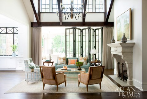 Touches of blue and orange, favorites of the homeowners, pop from the Christopher Norman pillows on the Travis & Company upholstered sofa. Matching wooden-framed Kravet chairs covered in Vervain fabric complement the Mr. and Mrs. Howard for Sherrill Furniture skirted blue chair. Art by Carol Bodiford from Anne Irwin Fine Art hides a flat-screen TV.