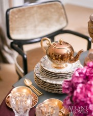 Influenced by the way their clients would live and entertain their guests, the design team infused a sense of history, color and pattern into this tablescape with a powerful mix of finery, from vermeil Tiffany flatware, radiant gilt urns and vases to interesting vintage and antique china. Rich and royal, indeed!