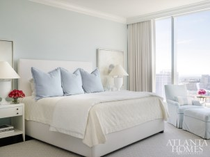The master bedroom's light-blue walls not only pull in the color scheme from the nearby living room but also add dimension to the space. Bedside vignettes include nightstands from Hickory Chair and art by Barbara Brenner through Bill Lowe Gallery.