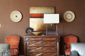The study's walls remain upholstered in the handsome chocolate-brown houndstooth Carithers originally chose, but the built-ins are freshly painted gray, with a terra-cotta backdrop. Kirkland decided to swap their existing store of tomes with the vast collection of pottery previously installed at the homeowners' mountain house. Here, the silhouettes pop against the rusty hue. This color also graces a group of vintage chairs in a Romo velvet. The wooden panels were sourced from The Signature in Buckhead.