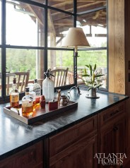 In the kitchen, a steel-framed box bay window takes center stage, opening to the covered terrace.