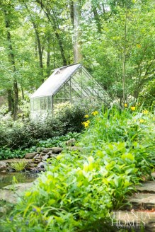The McWilliamses' greenhouse is encircled by yellow flag iris, frothy white viburnum and a stone-shrouded pond.