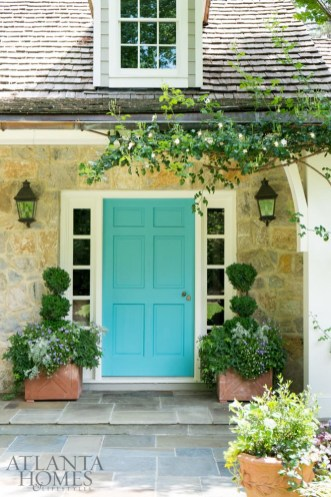 A bright turquoise front door is framed by intricate plantings.