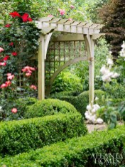 A cedar arbor presides over clipped boxwoods and climbing roses.