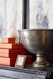 Among the dining room's beautiful vignettes is a treasured vintage ice bucket and a collection of Hermès boxes atop a refinished cabinet from Scott Antique Markets.