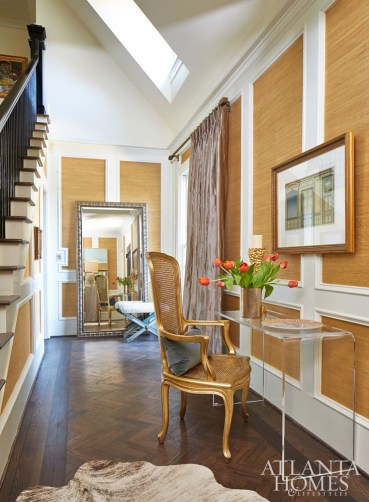 The foyer gets the golden treatment thanks to a luxe grasscloth wallcovering and a refinished vintage chair.