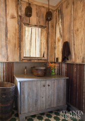 While the home's rustic atmosphere is present in this bath via corrugated metal wainscoting, it is tempered by a mosaic tile floor.