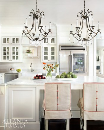 Kasler subtly incorporated Meghan's favorite hue into the kitchen via terracotta Marvic contrast fabric on the feminine counterstool slipcovers. Chandeliers, Dennis & Leen through Jerry Pair. Cabinet hardware, Matthew Quinn Collection.