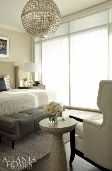 A wing chair from Baker and stone side table from Noir provide a relaxed sitting area in the bedroom.