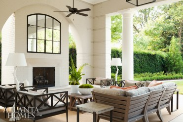 The fireplace wall, framed by a graceful archway, cleverly hides a television behind mirrored panels designed by architect D. Stanley Dixon. Accents you might expect to find inside the house abound, including a pair of ceramic floor lamps.