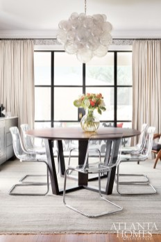 The dining room is a captivating space featuring a Muriel bubble chandelier from Oly, custom furniture, and the homeowner's existing acrylic and chrome chairs.