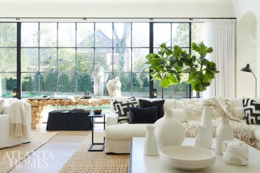 In the lofty living room, sunlight streams through floor-to-ceiling windows and reflects off custom plaster walls, which continue up to the ceiling seamlessly without trim. Turner selected white furnishings with pops of black for a crisp sense of cohesion, while texture in the form of a knotty wood console, jute rug and vintage finds such as a string of beads and a headdress from Africa create sensual appeal.