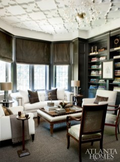 Handsome with its rich wood finishes, the library is undeniably an evening room in which to curl up with cocktails. Armchairs feature an iridescent alligator-effect fabric and were culled from the clients' personal belongings. Tufted Chesterfield sofa, Bungalow Classic. Leather-top tray table, Madeline Stuart through Jerry Pair.