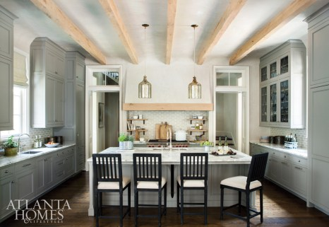 A shining example of the house's striking architectural design is the kitchen, where traditional transom windows allow extra light at the room's high points and unfinished wood ceiling beams and custom cabinetry continue along a strong central axis. The barstools are Restoration Hardware, and the smoked-glass ceiling pendants are by Arteriors through Bungalow Classic.