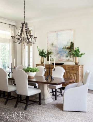 """As frequent entertainers, the homeowners relish having both casual and formal dining areas. The buffet was one of Westbrook's finds from Provenance Antiques. """"It's important to add that layer of texture and character that antiques bring to a space,"""" she says. The dining chairs are from Bungalow Classic, and the iron chandelier is Paul Ferrante through Ainsworth-Noah."""