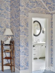 "Blue-and-white toile by Cowtan & Tout wraps a guest bedroom. ""At first, we were only going to cover the walls; then we realized it would make more of a statement if we went up and covered the eaves as well,"" says Weaks."