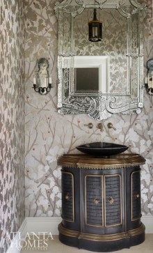 The powder room makes a glamorous statement with its silverleaf Nina Campbell wallpaper. The vanity is a retrofitted antique metal French heater cover from Parc Monceau.