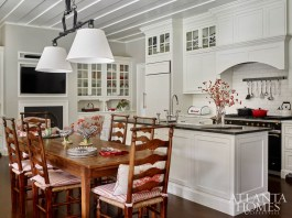 "The white kitchen is framed with black in the countertops and La Cornue range, with punches of Beverly Ellars' favorite color, red. ""We took shades of red and let it wind throughout the entire house,"" says Weaks."