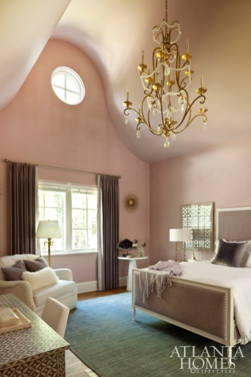 This pretty-in-pink bedroom, painted Sonoma Clay by Benjamin Moore, is outfitted for the homeowners' young daughter with a Hickory Chair bed, complementary blue rug by Keivan Woven Arts and dainty chandelier from Circa Lighting.
