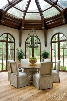 Inspired by the Biltmore Estate's interior conservatory, architect Bill Harrison designed a breakfast room with sweeping mahogany arches, while interior designer Karen Ferguson outfitted the sun-drenched space with fade-resistant Schumacher fabric on Formations chairs.