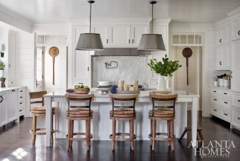 The layout of the kitchen was left intact but was updated with beadboard paneling, new appliances, marble surfaces and hardware. The spacious island, which had been previously stained, is now painted, and metal shades hang above. Old pizza paddles make a sculptural statement on the walls.