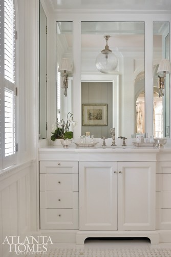 The master bathroom was completely gutted and now sparkles with gleaming tile, white cabinetry and mirrored surfaces and furniture.
