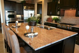 The warm granite countertop by AA Marble & Granite (dba Andrews & Associates) is complemented by a tile backsplash in this contemporary kitchen.