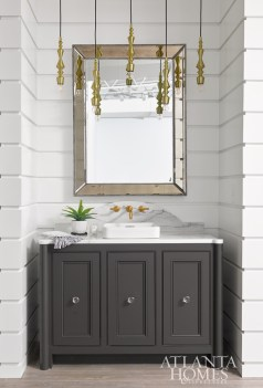 A wall-mounted faucet and vessel sink from Kohler are striking atop custom cabinetry painted Sherwin-Williams Urbane Bronze.
