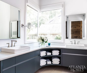 """""""With modern homes, you can get away with doing two corner windows like in the bathroom,"""" says Patrick of the unique window layout. The goal was to keep the room sophisticated but pared down, using simple can lighting, LED mirrors and hardware-free cabinets, which are painted a serene Down Pipe by Farrow & Ball."""