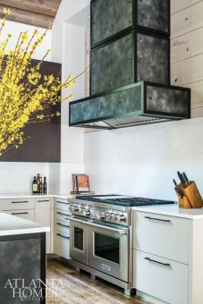 The elongated, chimney flue–style hood isn't just for aesthetics; the exhaust travels through what appears to be a second exterior chimney crown.