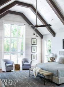 Most of the furnishings in the master suite were repurposed from the couple's previous home. The whitewashed back wall and ceiling created a dreamy, soft palette that pairs well with the room's contemporary finishes, such as the ceiling fan, structural lines on the headboard and seating, and lack of heavy draperies.