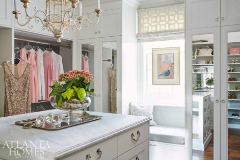 """When Quinn discovered the homeowner's flair for fashion, he designed a showroom-like space to store and display her wardrobe and accessories. To match her unique organization process, Quinn added a combination of closets, open shelving and hanging racks, as well as a glass-lit Lucite purse shelf. """"Design details, like Lucite pulls, light and bright walls, and the chandelier, prevent the clothes from dominating the space,"""" says Quinn."""