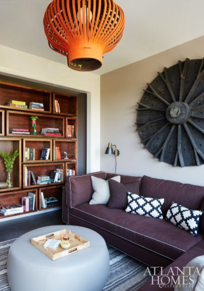 Khandwala went for a cozier feel in the den, where a 1920s machine mold serves as artwork above the sofa. The bookshelf was custom designed by Khandwala through Made Again. Leather ottoman, Room & Board. Chandelier, BuzziBoutique.