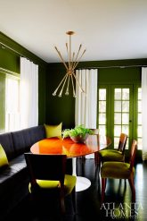 Dramatic walls (painted Avocado by Benjamin Moore), a streamlined banquette and velvet upholstered vintage chairs add an enveloping feel to the otherwise formal dining space.