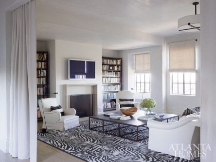 While the majority of the residence retains an ethereal gray color palette, color is introduced into the library through the client's textbook collection.