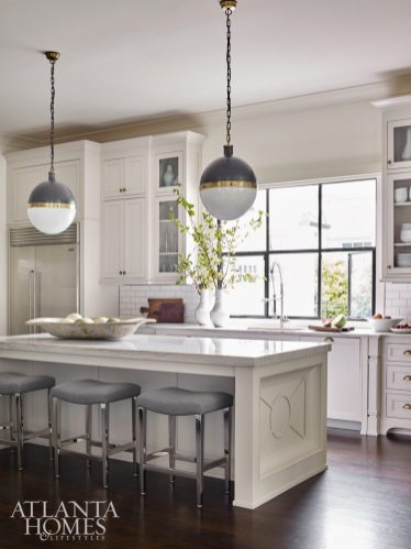 Bernhardt barstools sidle up to a custom countertop by builder Monte Hewett Homes. Visual Comfort pendants add contrast to the white kitchen, while subway tile adds a timeless layer. Cutting boards from Robuck. Montes Doggett pottery from B.D. Jeffries.